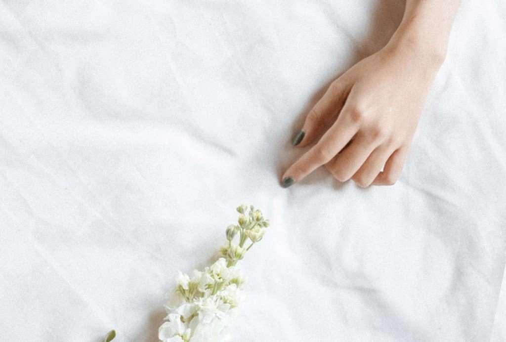 mano en sabanas blancas